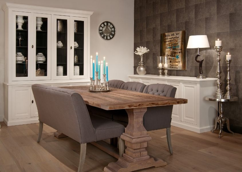 Farmhouse dining table with grey fabric chairs and large white display cabinet