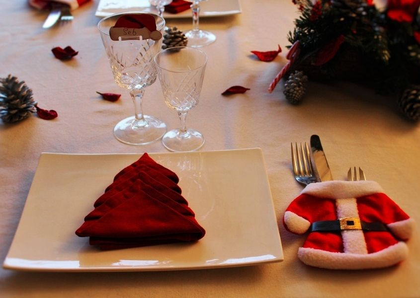 Close up of dinner table with red Christmas tree shaped napkin and Father Christmas cutlery pocket