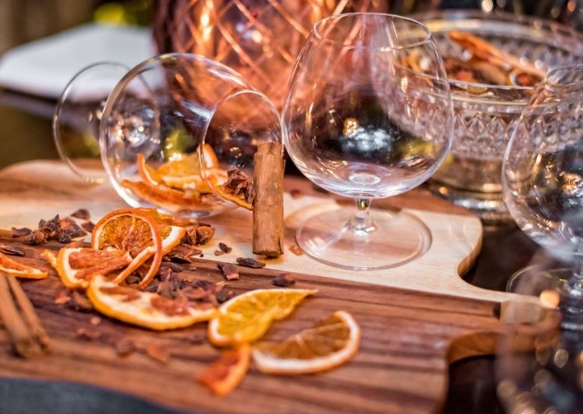 Dried orange slices and cinnamon sticks on wooden dining table with brandy glasses