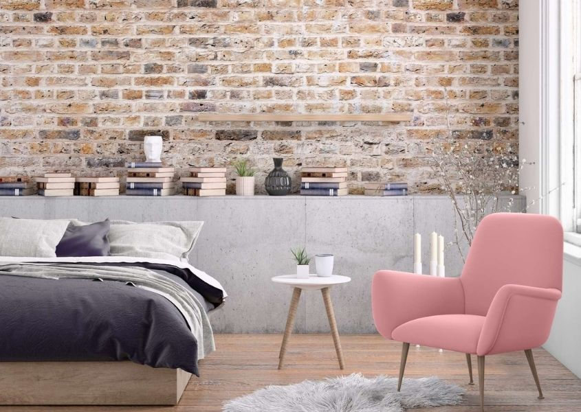industrial bedroom with exposed brick wall and pink armchair