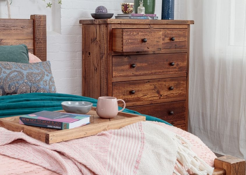 wooden chest of drawers with wooden bed and pink covers