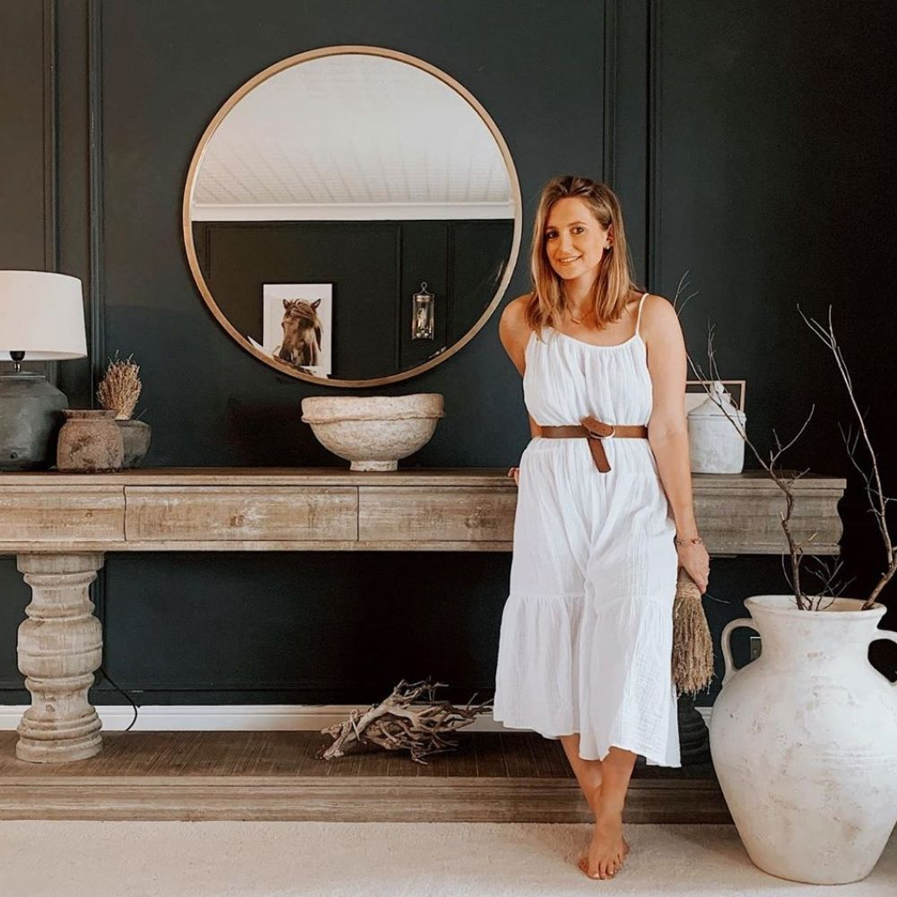 Women in white dress standing in front of large reclaimed wood console table and round wall mirror