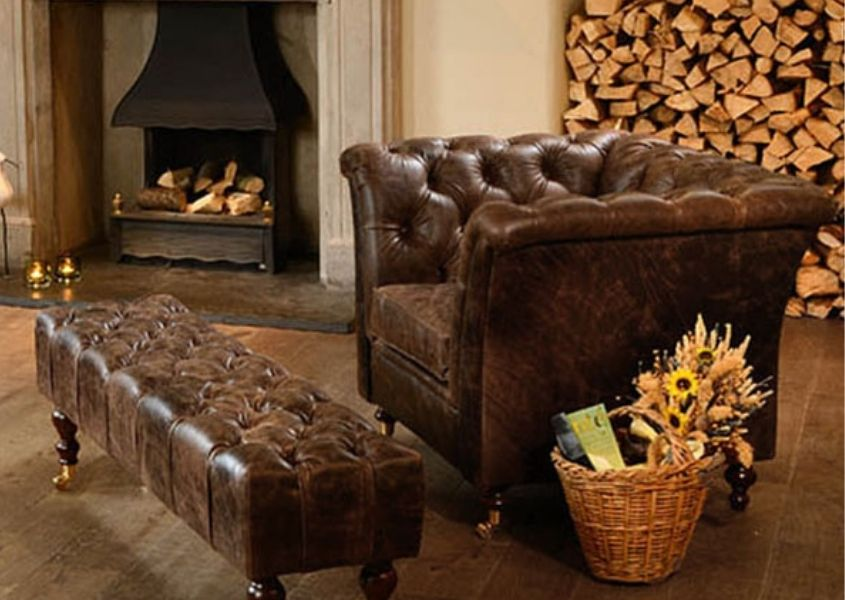 Brown leather chesterfield armchair and footstool in front of open fire