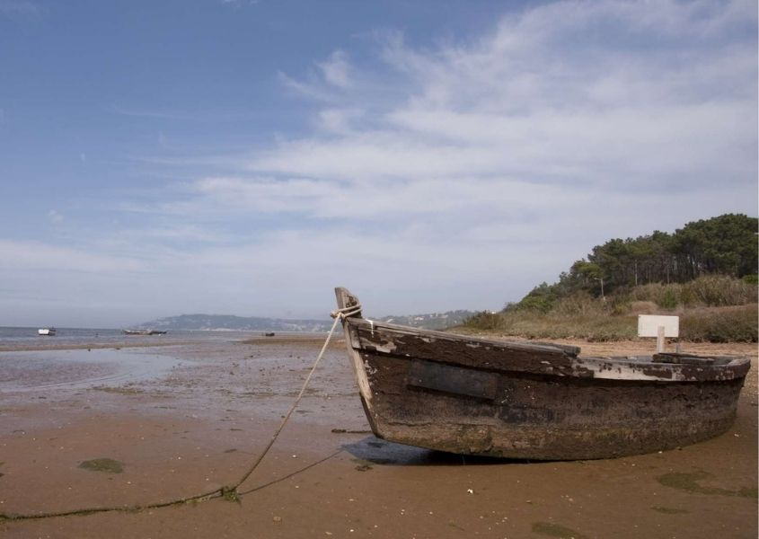 Sandy beach with old wooden boat on shore