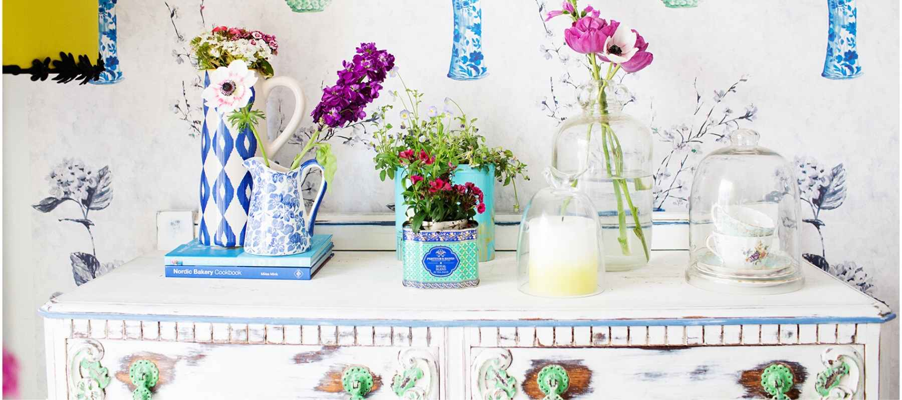 Colourful pots and vases with flowers on white dressing table