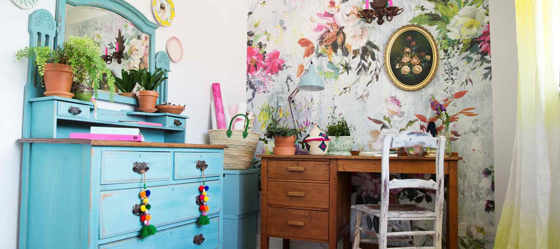 Blue painted chest of drawers with wooden desk and floral wallpaper