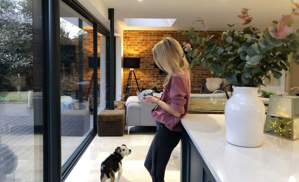 Woman leaning against kitchen island with dog