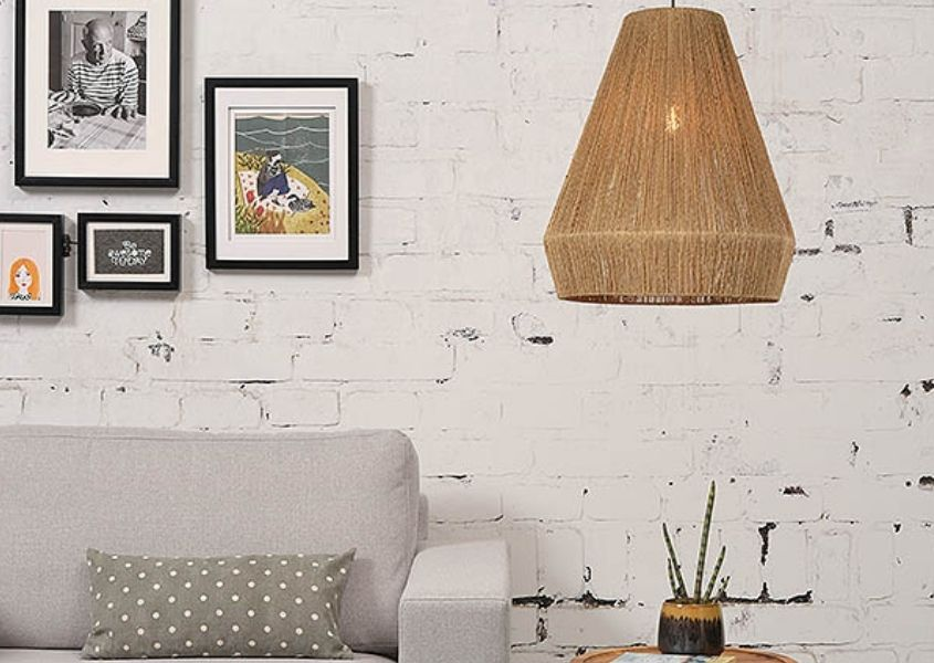 Jute hanging pendant light over side table next to a grey sofa