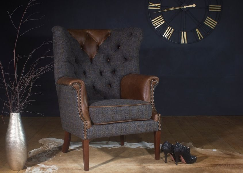 Harris Tweed and leather wing back armchair with wall clock in background