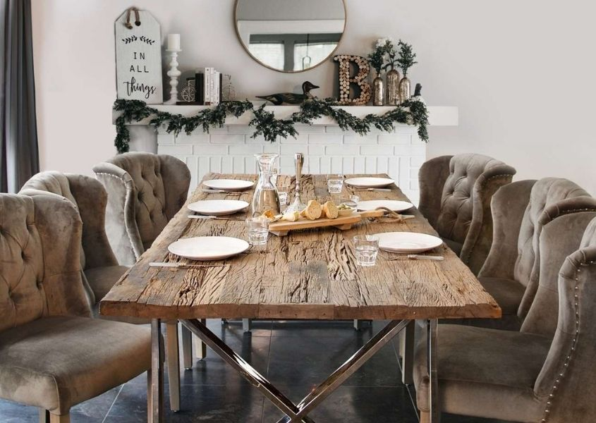 Reclaimed wood dining table with silver legs and taupe upholstered dining chairs in front of Christmas decorated fireplace