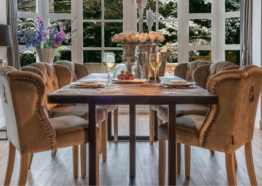Reclaimed wood dining table with velvet dining chairs and two glasses of white wine