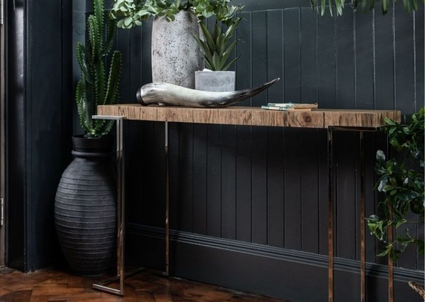 Rustic console table with shiny silver metal legs against a dark painted wall with a white vase and green plant