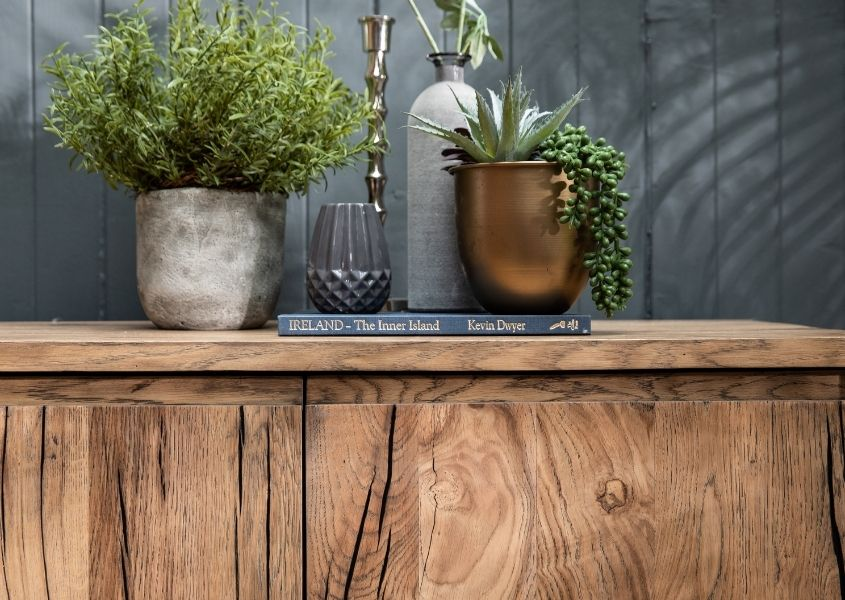 Close up of reclaimed wood sideboard with green plants in stone pots