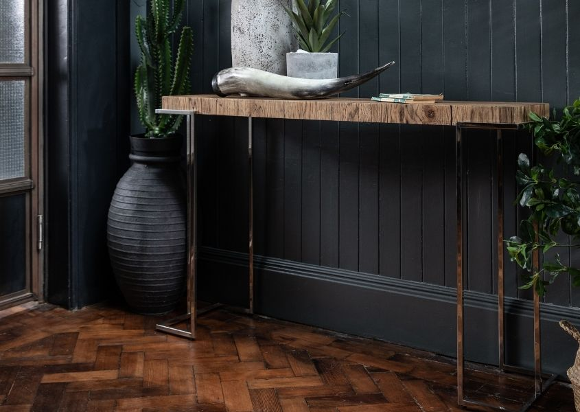 Tall reclaimed wood console table with long thin polished metal legs in hallway with dark grey walls