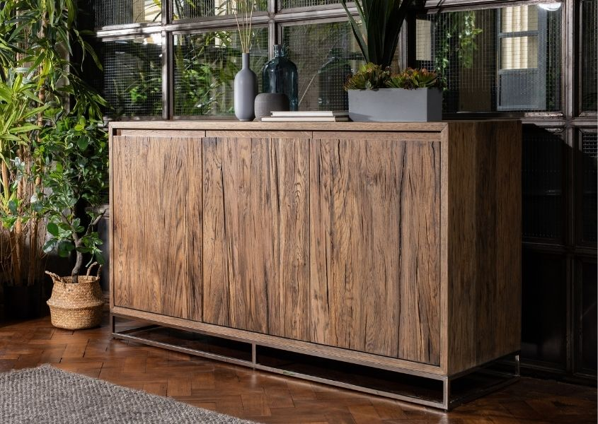 Large reclaimed oak sideboard with green floor plant and ornaments on top