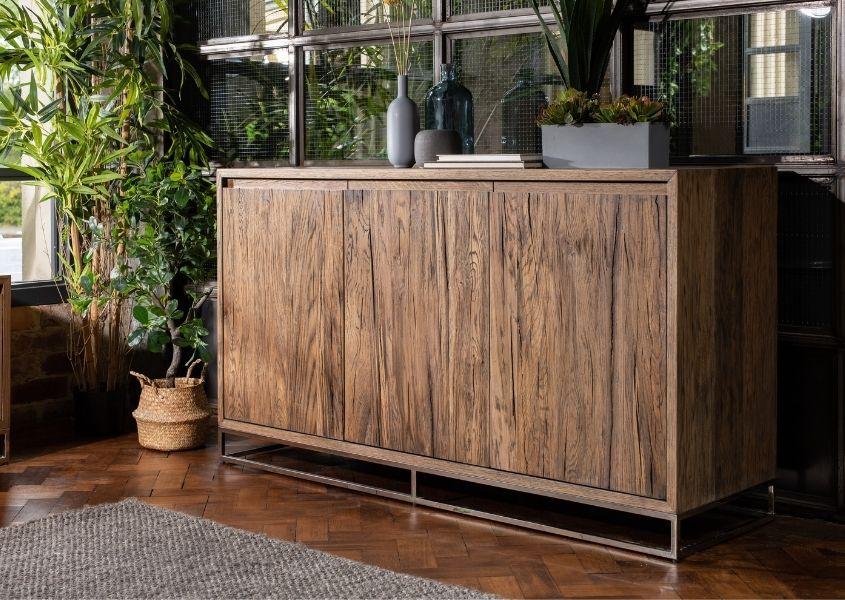 Reclaimed wood large sideboard against dark wall with green plants