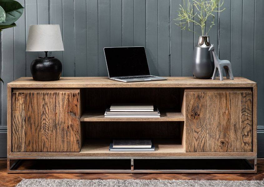 Reclaimed wood TV unit with two cupboards and middle shelf, with laptop and lamp on top
