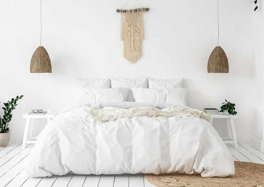 White scheme bedroom with two rustic hanging pendant lights and wall art