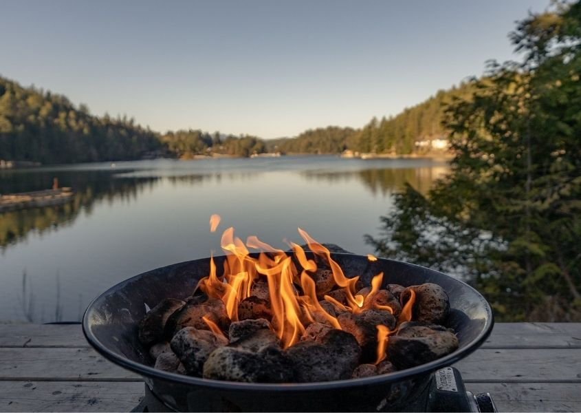 Round fire pit with flames next to a wide lake