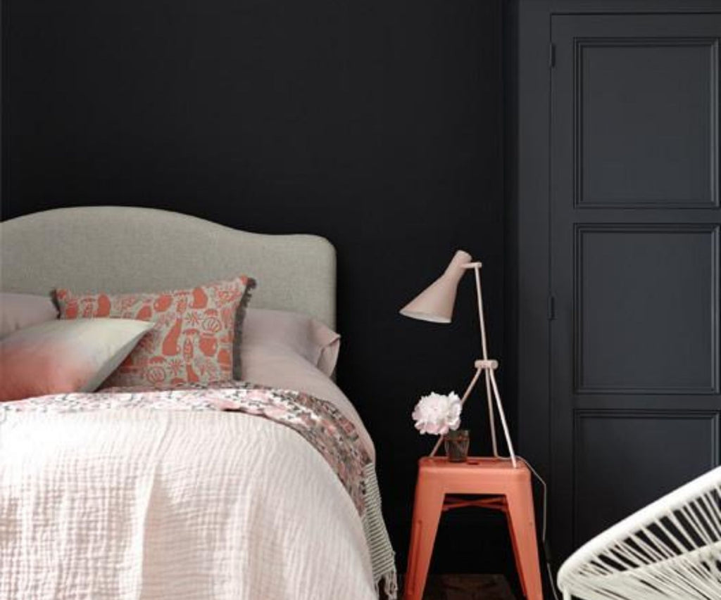 Bedroom with dark grey walls and pink bed covers