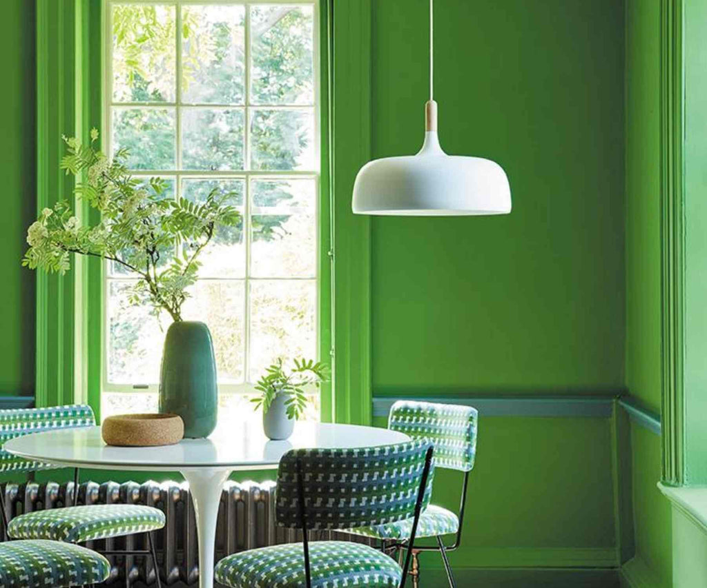 Bright green painted walls with white dining tale and white hanging light