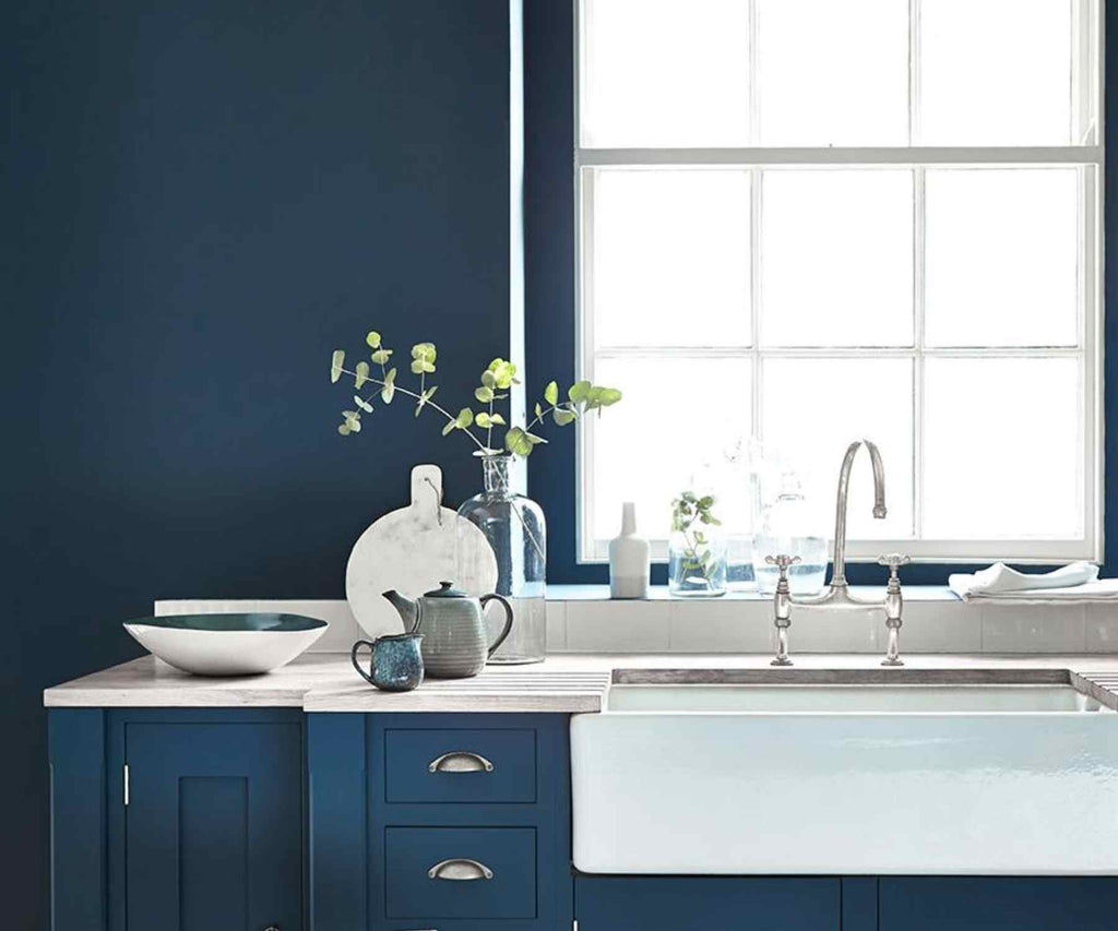 Dark blue painted wall and kitchen unit with white belfast sink