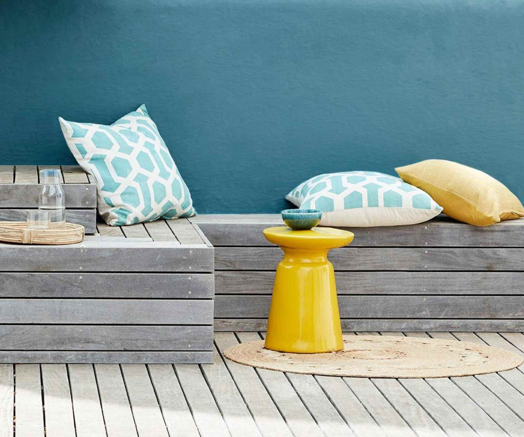 Deep blue outside wall with wooden bench and yellow accesories