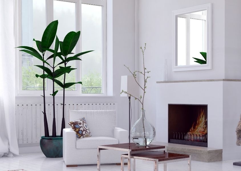White living room with white armchair, mirror of fireplace and large green plant