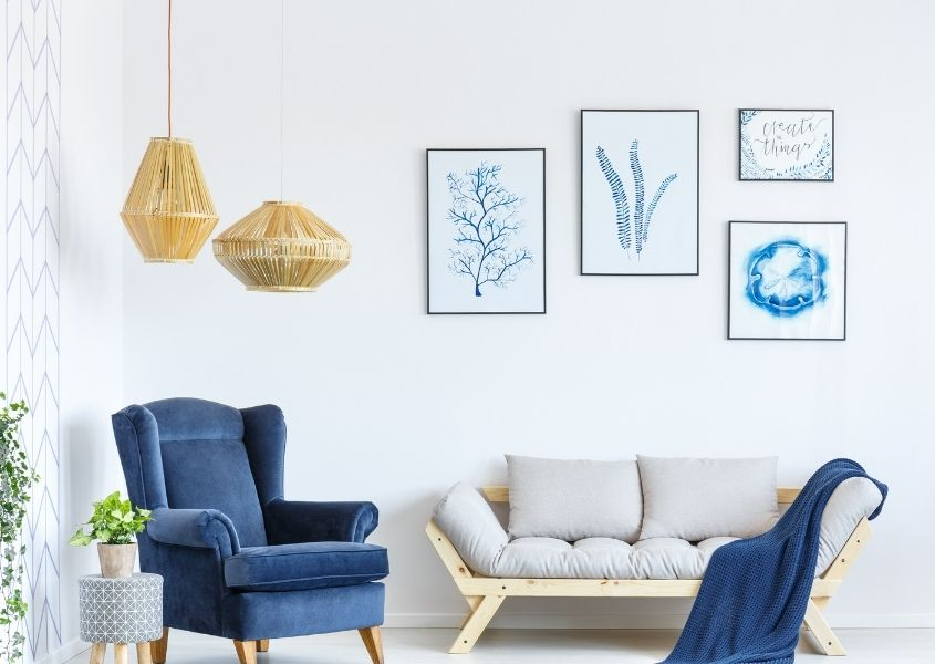 Natural hanging pendant lights in living room with bright blue wing back armchair and light grey sofa