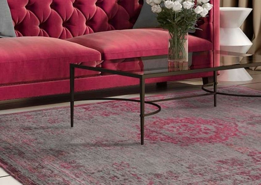Faded pink rug with glass coffee table and pink velvet sofa