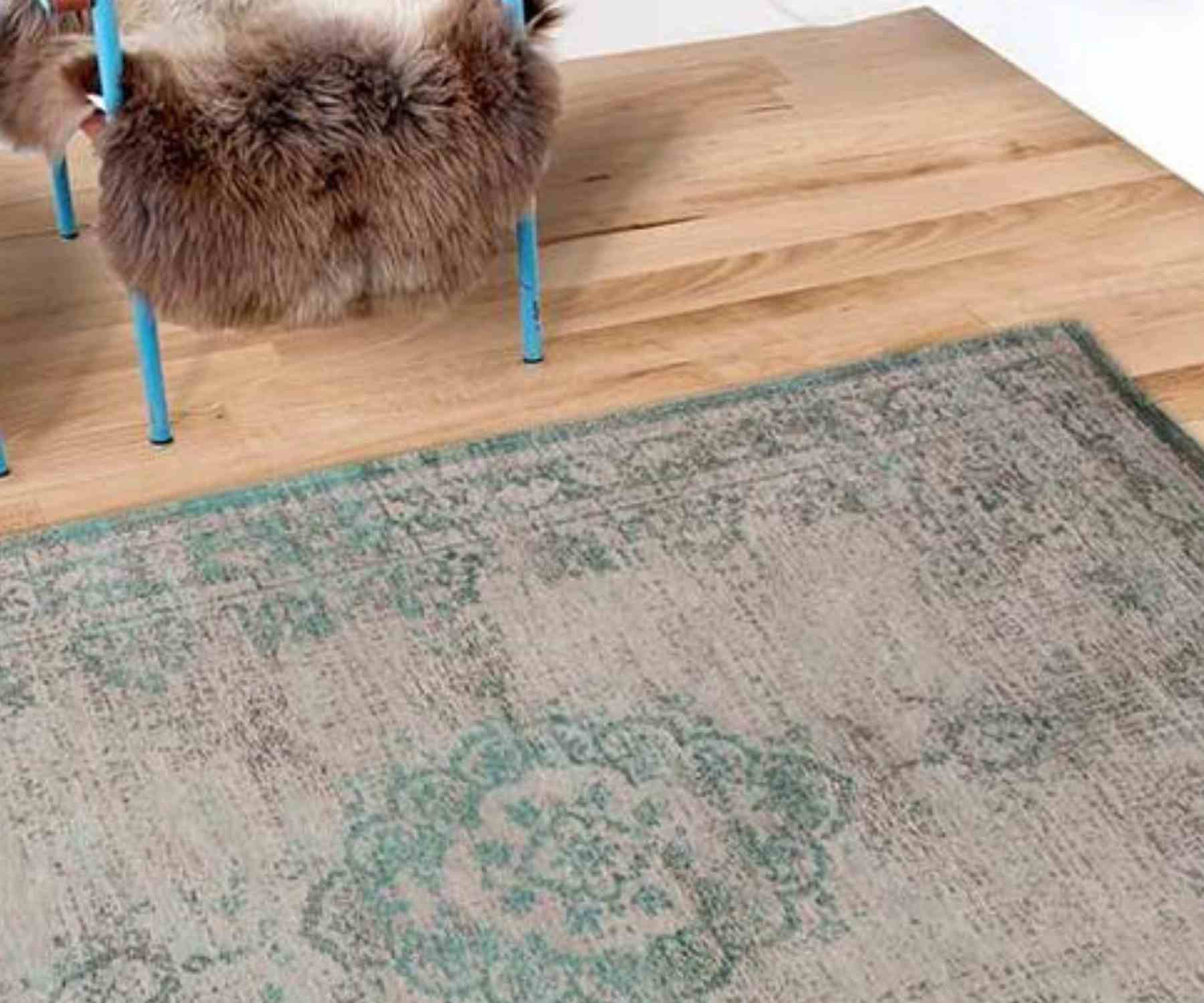 Faded green rug on wooden floor with metal chair and fur throw