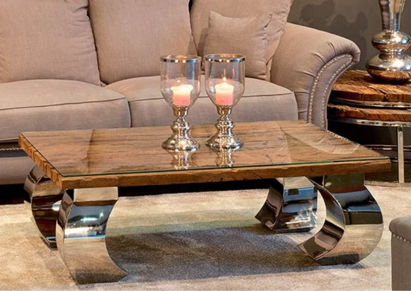 Wooden coffee table with thick shiny metal curved legs with candles on top