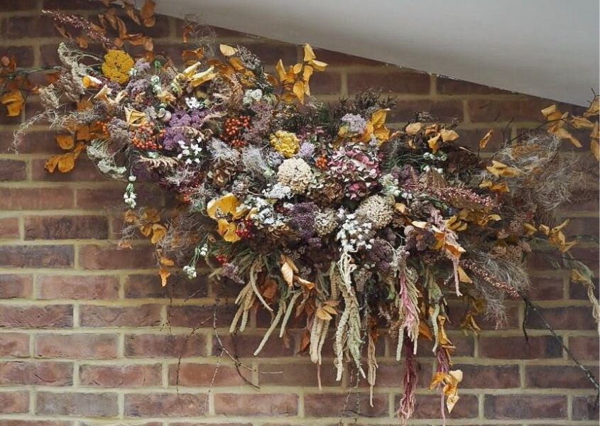 Large dried flower art installation against exposed brick wall