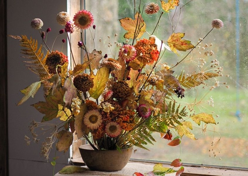 Brown vase with bouquet of dried flowers in front of window
