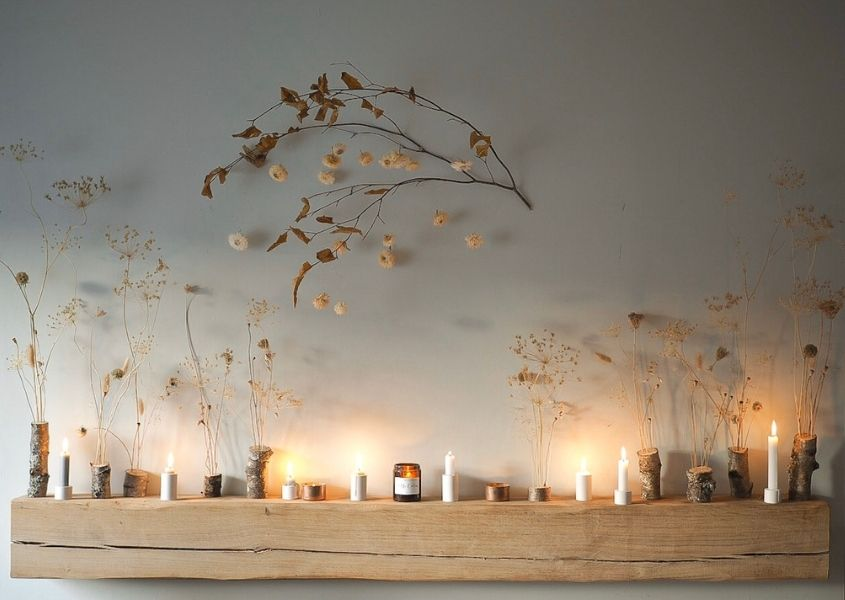 Wooden mantlepiece with arrangement of dried flowers and tea lights
