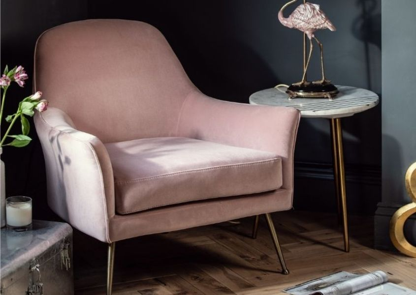 Pink velvet armchair in room with dark walls and flamingo side lamp