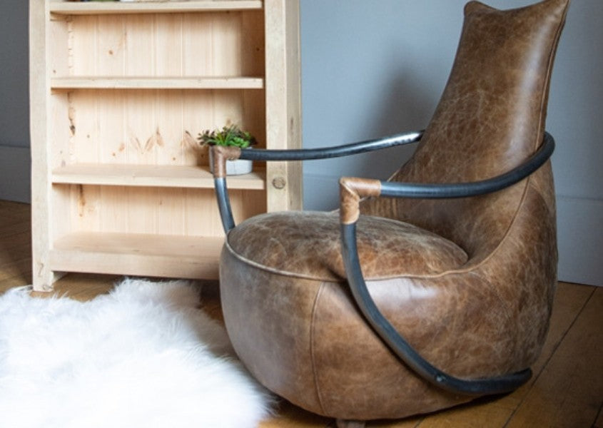 Brown leather armchair with metal arms with white sheepskin rug