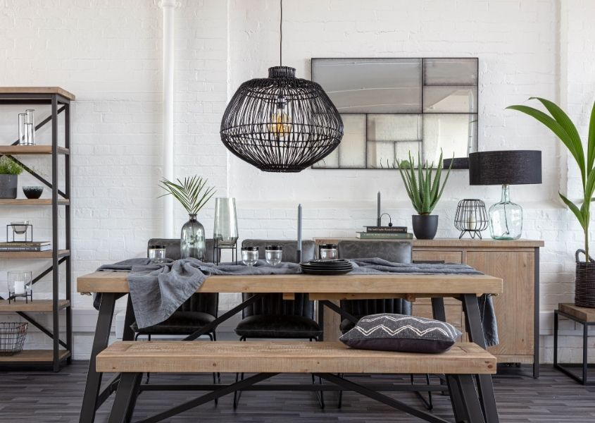 Black bamboo hanging light over an industrial dining table with rustic top and black steel frame with matching wooden bench
