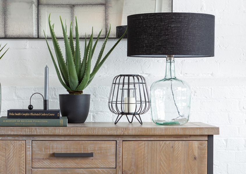 Recycled glass table lamp on top of wooden sideboard with aloe vera plants and other ornaments