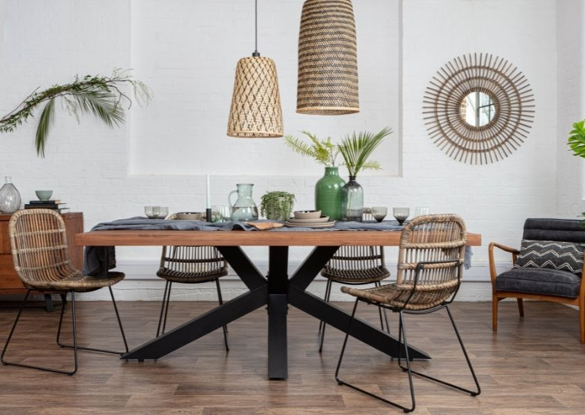 industrial dining table with black metal spider legs and rattan hanging pendant lights
