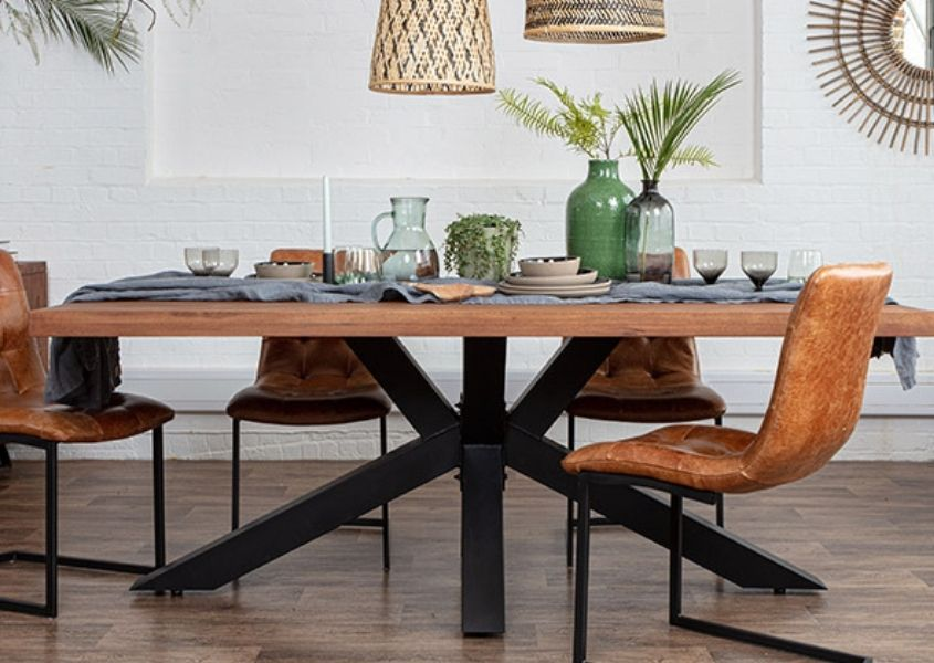 Wooden dining table with black steel spider leg and tan leather industrial dining chairs