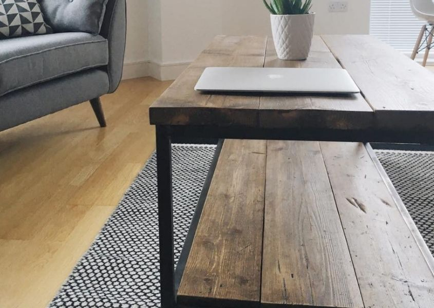Close up of industrial reclaimed wood coffee table on grey rug