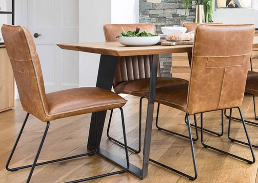 Brown faux leather dining chairs with black steel legs and industrial dining table