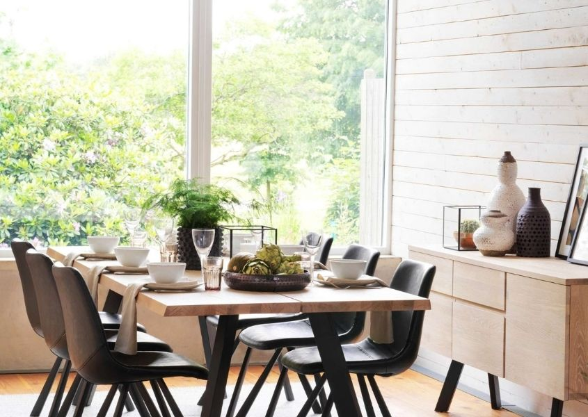 Wooden industrial dining table with black metal legs and dark faux leather dining chairs in front of large glass window
