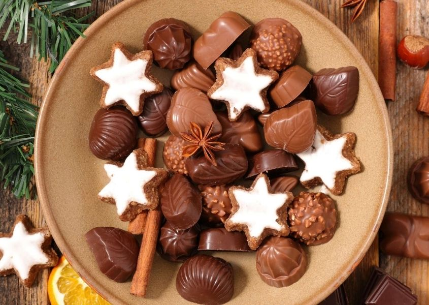 Assortment of milk chocolates and white star biscuits on a brown plate