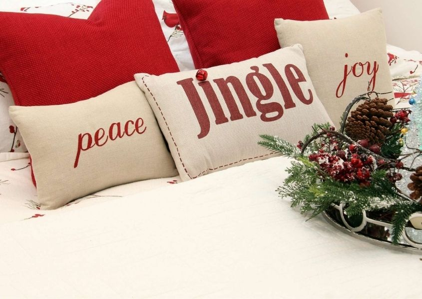 Red and white Christmas cushions on white bed covers