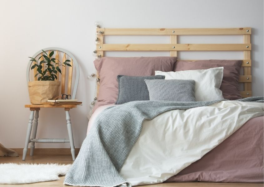Wooden bed with palette headboard and painted wooden spindle chair with plant as bedsidetable