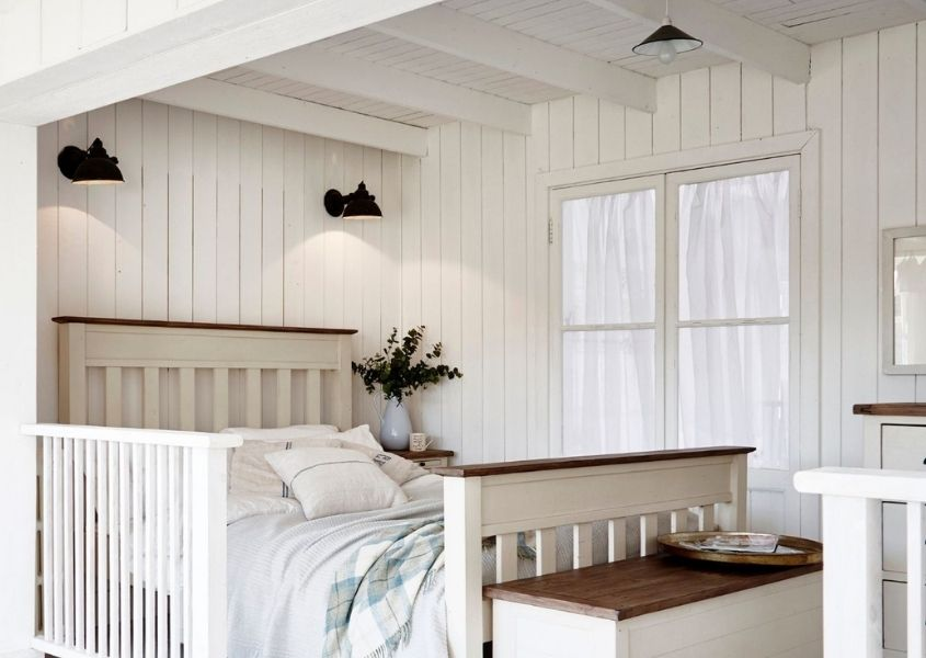 White bedroom with white panelled walls and wide wooden bed.