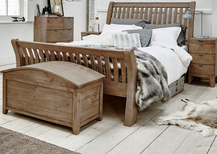 Reclaimed wood bed with matching blanket box and bedside tables with brown faux fur throw on bed