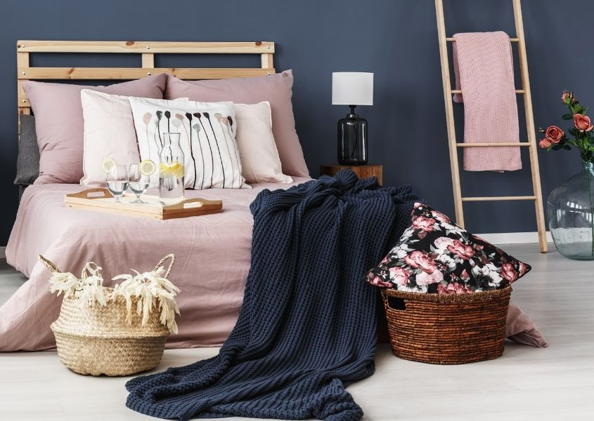 Bedroom with dark blue painted wall, wooden bed and wicker baskets on the floor with blue blanket hanging off floor.
